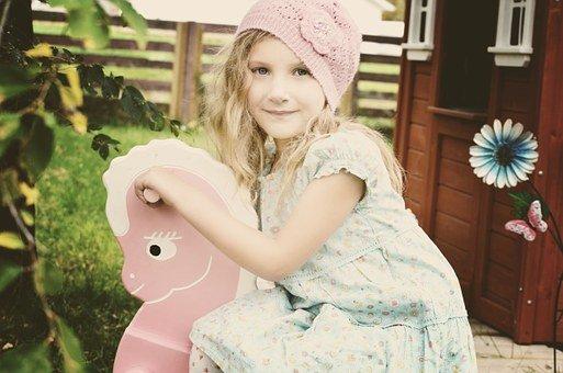 holčička venku na houpacím koníkovi